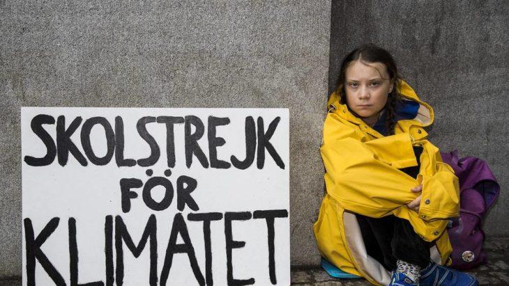 Greta Thunberg sentada en una banqueta con un letrero de su protesta de los viernes