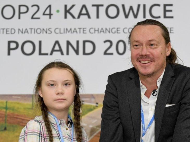 Greta Thunberg con su padre con una lona de fondo de un evento de la ONU en Polonia 2018