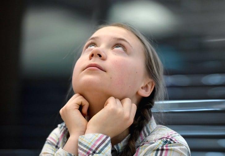 Greta Thunberg con camisa de cuadros apoyada en sus brazos mira hacia el techo
