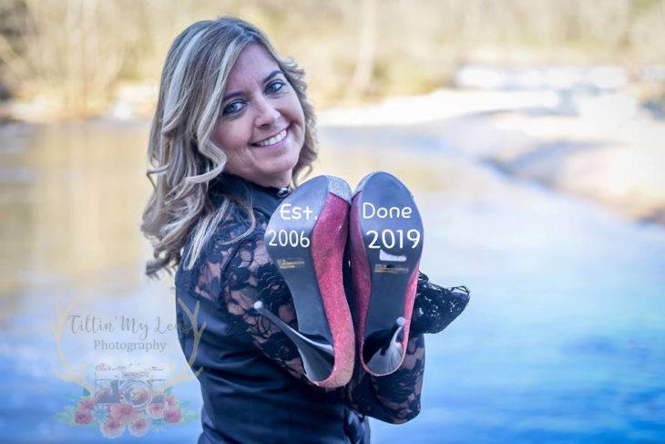Marie Lollis parada frente a un lago con sus zapatos en la mano con la fecha de inicio y final de su matrimonio