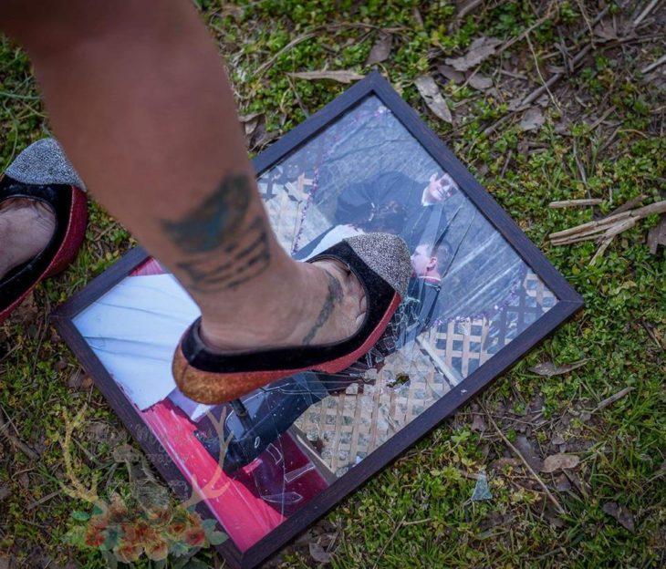 Un pie sobre una foto en un portarretrato quebrado