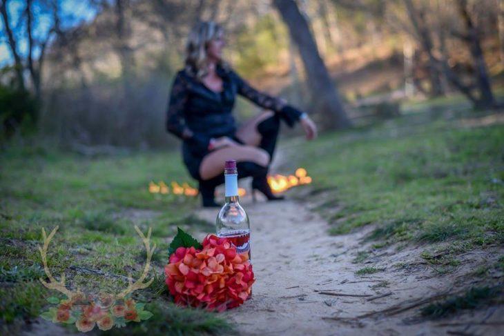 en primer plano un ramo de flores y una botella de vino, en segundo plano Marie Lollis en cluquillas