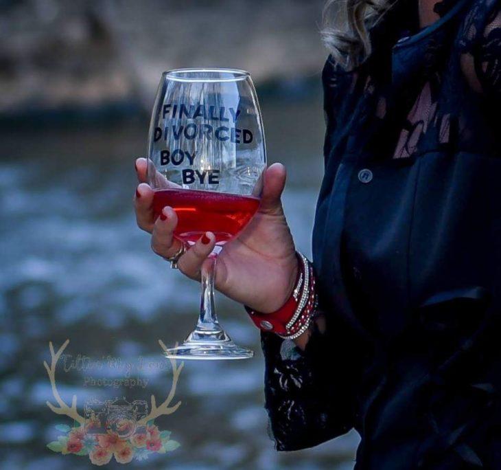 una mano con una copa de vino que dice 'finally divorced bye boy'