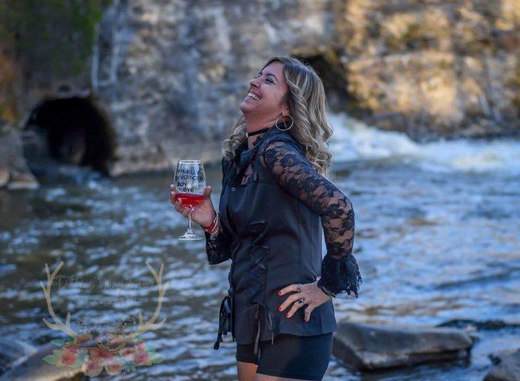 Marie Lollis a la orilla de un cuerpo de agua con una copa en la mano riéndose
