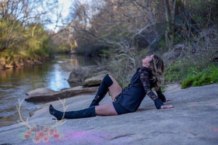 Marie Lollis recostada sobre una piedra plana a la orilla de un arroyo