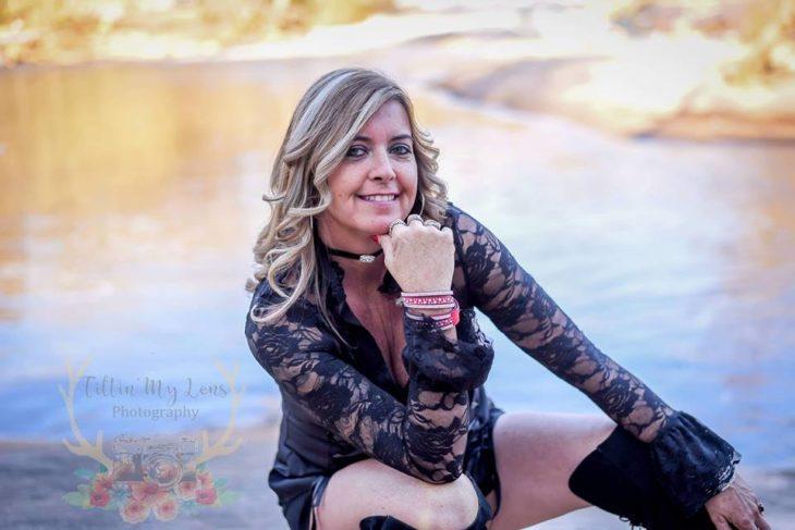 Marie Lollis en clucillas apoyada en una de sus manos frente a un pequeño lago