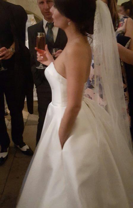 Foto de una novia en una fiesta con una mano dentro de las bolsas de su vestido de novia, en la otra sostiene una copa
