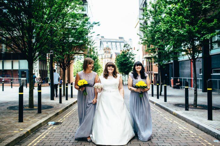 una novia y sus dos damas caminan por una calle, la novia lleva las manos en sus bolsillos y las damas llevan ramos