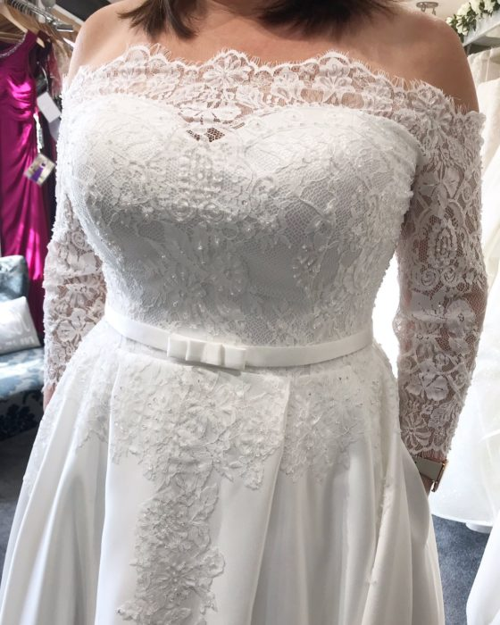 Torso de una mujer de talla grande en vestido de novia con las manos dentro de los bolsillos del vestido