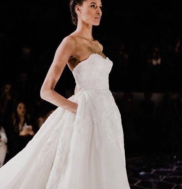 Una modelo en una pasarela lleva un vestido de novia con bolsillos en los que lleva las manos metidas