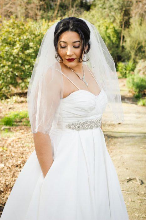una novia posa en un jardín, con las manos dentro de las bolsas de su vestido