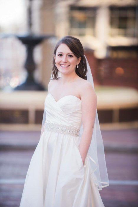 una novia posa con una fuente de fondo, lleva sus manos en los bolsillos de su vestido