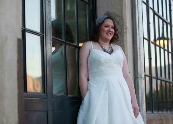 Una novia recargada en una puerta de un edificio posa con una mano dentro del bolsillo de su vestido y la otra a un costado de su cuerpo