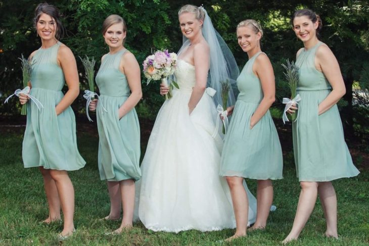 una novia y sus damas posan en un jardín, todas con la mano izquierda dentro del bolsillo de sus respectivos vestidos