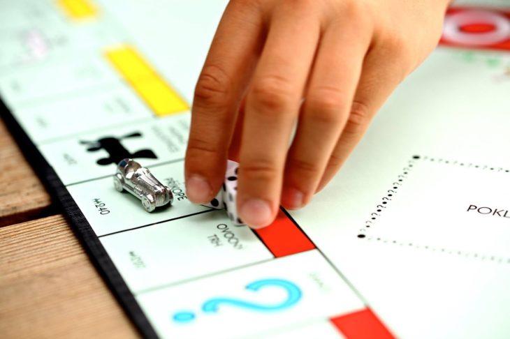 mano de una mujer tomando los dados de un juego de Monopoly