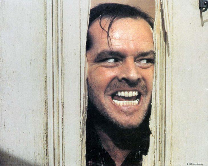 Jack Nicholson en la escena ícono de 'El resplandor' asomando la cara entre la puerta