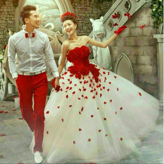 una pareja de novios orientales caminan a un costado de una escalera, él con pantalón rojo y ella con vestido blanco y detalles rojos