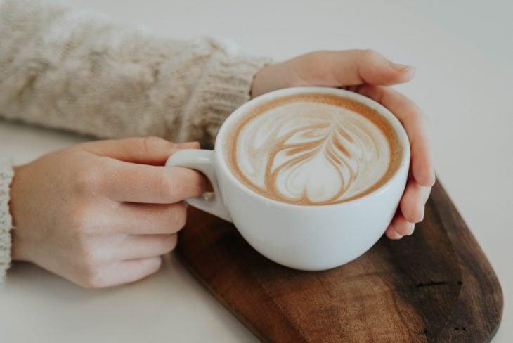 Manos de mujer sosteniendo una taza de café