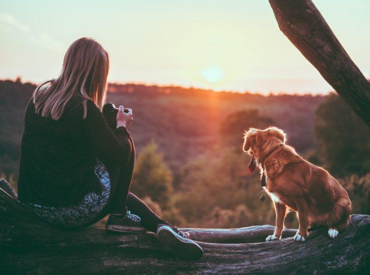Mujer rubia con su perrito viendo el atardecer