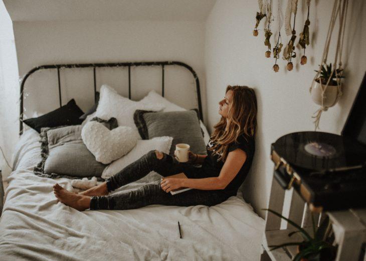 Mujer sentada en una cama con una taza de café en la mano