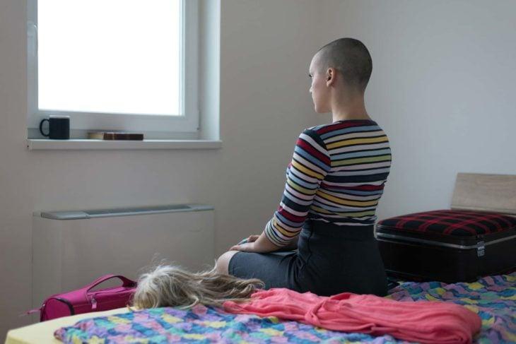 Mujer sentada en la orilla de la cama con su cabello rapado y con una peluca al lado