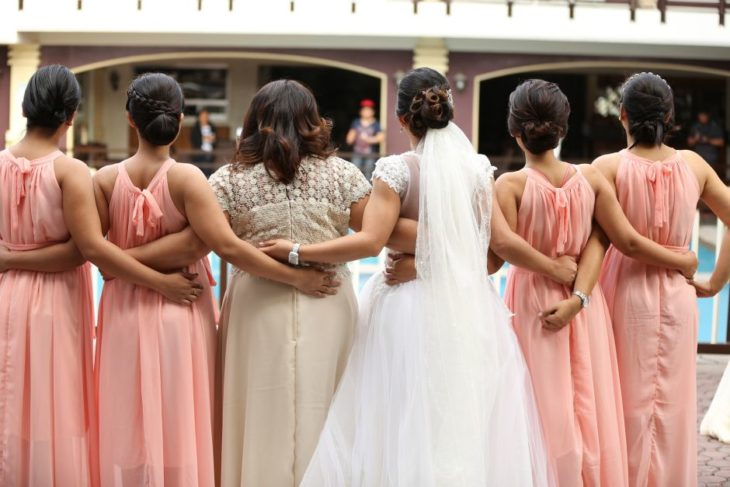 Novia abrazando a sus damas de honor mientras posan para una fotografía