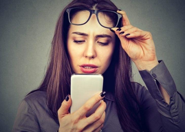 mujer viendo el celular con gesto sorprendido