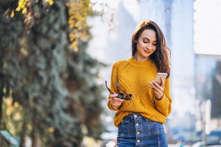 Mujer viendo su celular mientras camina