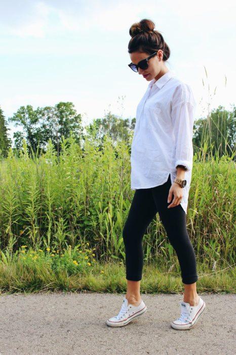 Chica usando unos leggins, camisa blanca y tenis converse