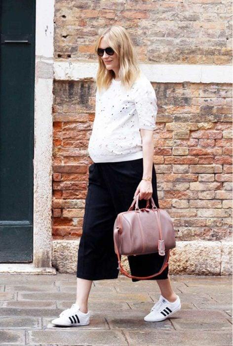Chica embarazada caminando por la calle mientras usa unos pantalones culottes, sueter y tenis adidas