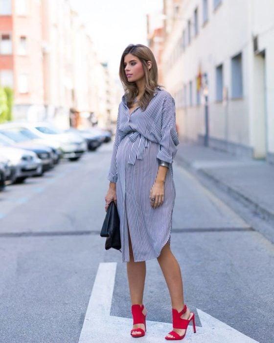 Chica embarazada posando para una sesión de fotos mientras modela un vestido de gasa en color azul y tacones en color rojo