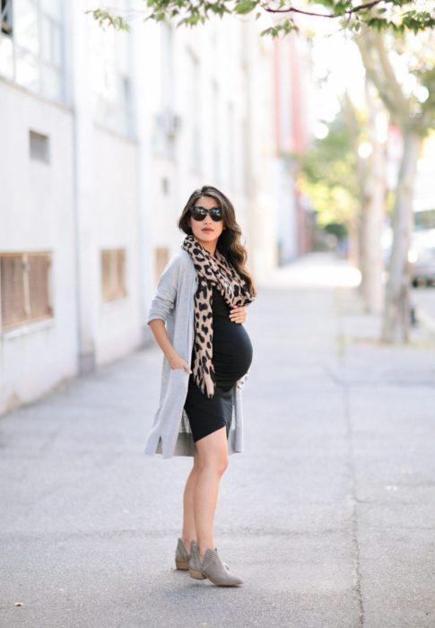 Chica embarazada parada e la calle usando un vestido negro con bufanda animal print y saco color gris