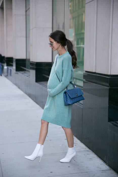 Chica usando un vestido largo color azul marino mientras está parada en la calle recibiendo una sesión de fotos