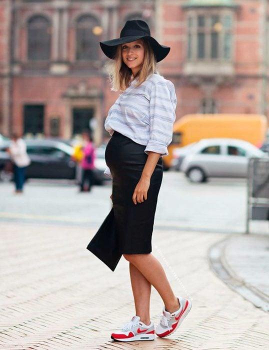 Chica usando un vestido de color negro con sombrero, tenis y una camisa blanca mientras está parada en una sesión de fotos