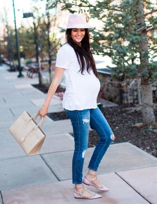 Chica embarazada usando una camisa blanca y jeans con sombrero