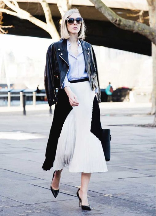 Chica usando una falda plisada con una chaqueta de cuero mientras camina por la calle