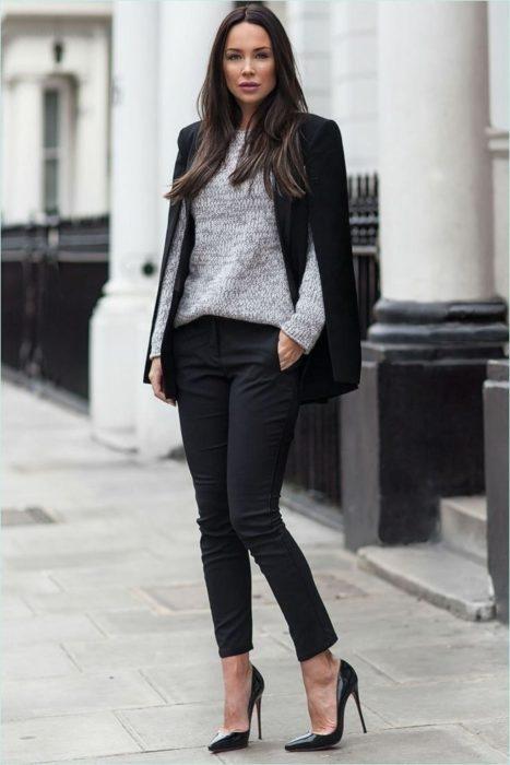 Chica usando un atuendo negro con un sueter de color gris mientras está parada en la calle