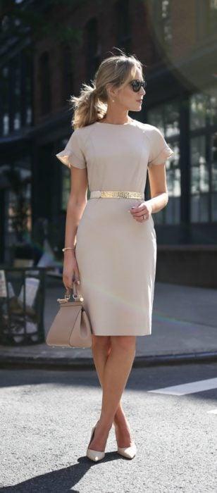 Mujer usando un vestido de color claro con un cinturón, bolso y zapatos del mismo colo r