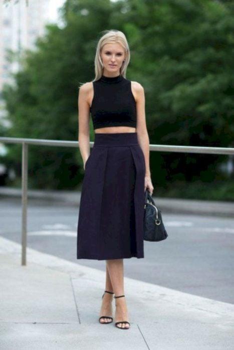 Chica usando una falda midi con un crop top de color negro mientras está parada en la calle