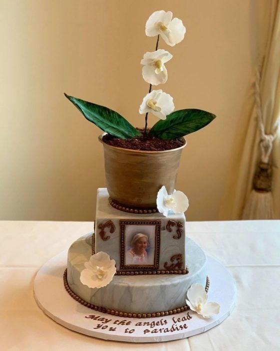 Pastel hiperrealista en forma de maceta con orquídeas y una fotografía