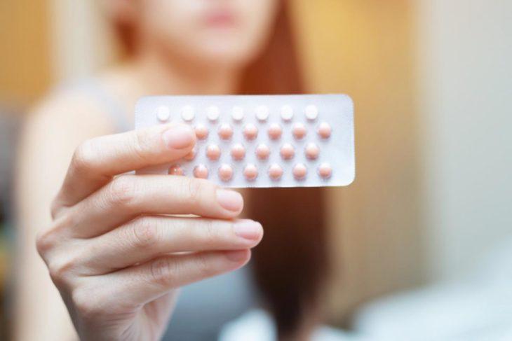 Mujer de fondo sosteniendo en su mano unas píldoras anticonceptivas