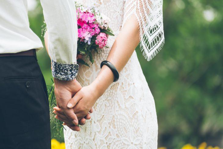 Manos de novio y novia entrelazadas