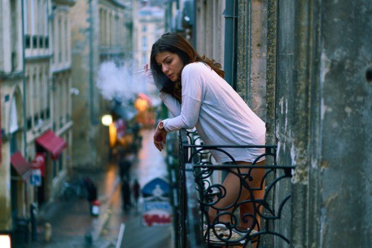 Mujer fumándose un cigarrillo en la terraza de la habitación