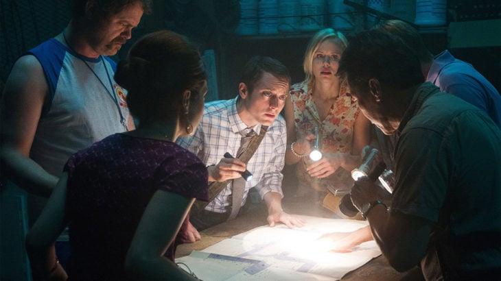 Escena de la película Infectados, Grupo de adultos mirando un mapa dentro de una biblioteca