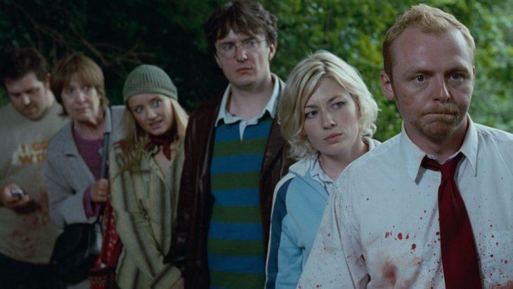 Escena de la película Zombies party, grupo de amigos escondidos tras unos arbustos