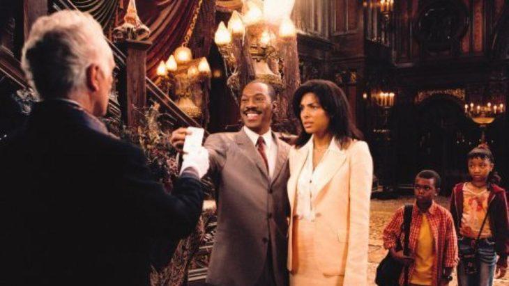 Escena de la película La mansión encantada, Eddy Murphy frente a unas escaleras de caracol abrazando a una mujer