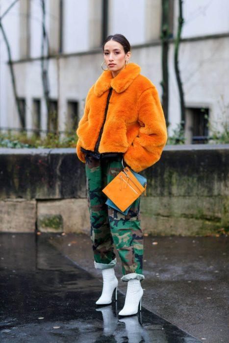Chica usando un abrigo de color naranja con un pantalón verde militar