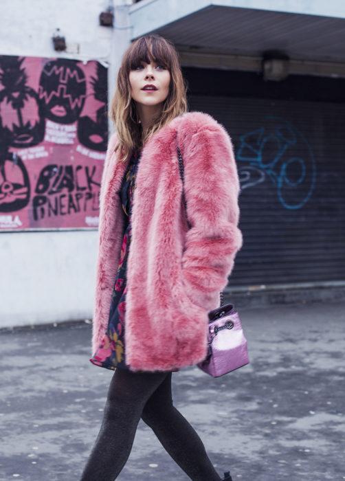 Chica usando un abrigo de color rosa mientras usa un outfit de color negro
