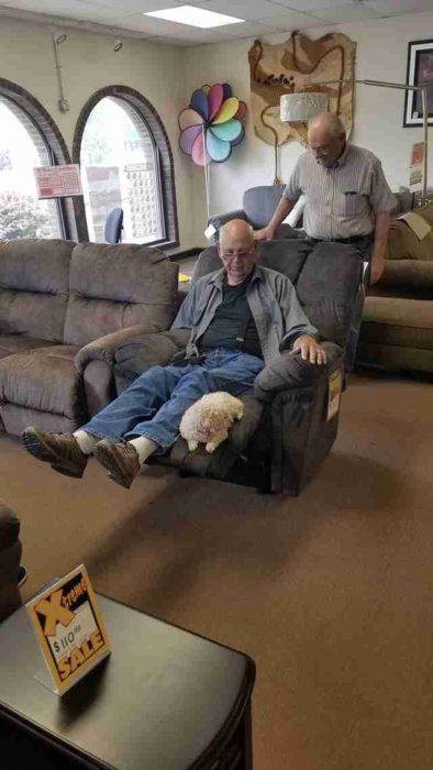 Abuelo recostado en un sofá reclinado mientras su perrito puddle está sentado al final del sofá