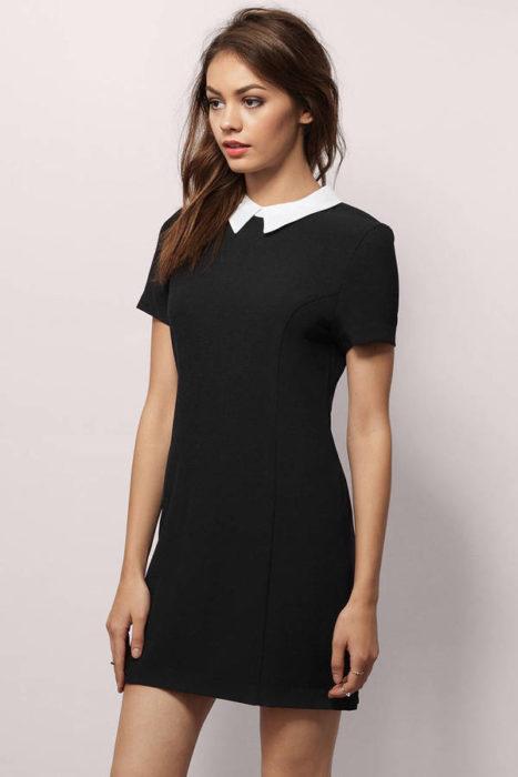 Chica modelando un vestido corto, negro, estilo merlina